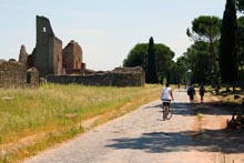 Two people riding bikes along the Appian Way